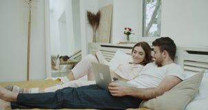 一对年轻夫妇的美好的早晨在床佩带的睡衣和做他们的读书和检查的惯例 影视素材