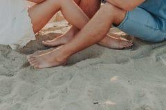 一对年轻夫妇的脚在赤足爱的,在沙子 免版税库存照片
