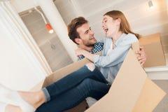 一对年轻夫妇移动向一栋新的公寓 人给一个新的家带来他的他的胳膊的女朋友 库存照片