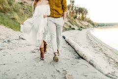 一对年轻夫妇获得乐趣并且走在海海岸线 看彼此的新婚佳偶与柔软 浪漫 免版税图库摄影