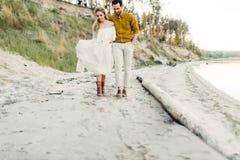一对年轻夫妇获得乐趣并且走在海海岸线 看彼此的新婚佳偶与柔软 浪漫 免版税库存照片