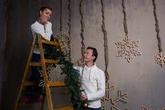 一对年轻夫妇装饰圣诞节的一个房子与诗歌选  免版税库存照片