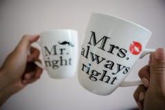 一对年轻夫妇运载的白色茶或咖啡与正确词的先生和夫人总是  库存图片