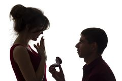 一对年轻夫妇,一个人身分在膝盖和提出一个提案的剪影对女孩,人给圆环并且要得到 库存图片