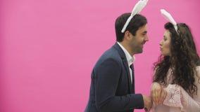 一对年轻恋人夫妇出现在桃红色背景,再生产野兔马  使用一只桃红色兔子的耳朵在的 股票录像