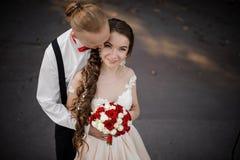 一对年轻愉快的已婚夫妇的顶视图与婚姻的花束的 免版税库存图片