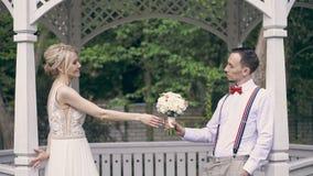 一对年轻美好的夫妇在眺望台站立,在彼此对面并且互相通过婚姻的花束 影视素材
