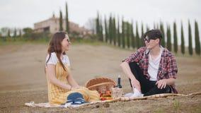 一对年轻谈的夫妇坐有的毯子在柏树的背景的一顿野餐 股票录像