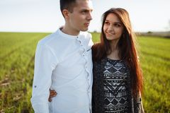 一对年轻,愉快,爱恋的夫妇,站立在一个绿色领域,反对天空在手旁边,和开心,做广告和  库存照片