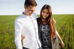 一对年轻,愉快,爱恋的夫妇,站立在一个绿色领域,反对天空在手旁边,和开心,做广告和  库存图片