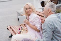 一对年长夫妇休息坐在正方形的一条长凳 妇女在她的手和微笑上拿着一种片剂 免版税库存照片