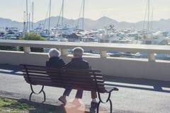 一对年长夫妇坐在白色昂贵的游艇和山中的一条长凳在一好日子 免版税库存照片