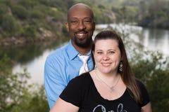 一对微笑的人种间夫妇的画象本质上 免版税库存照片