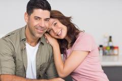 一对微笑的夫妇的画象在厨房里 免版税库存照片