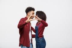 一对微笑的年轻非洲夫妇的画象在拥抱和显示与手指的便衣穿戴了心脏姿态 免版税库存图片