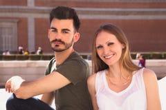 一对微笑的年轻夫妇的画象在城市 库存照片