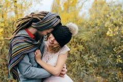 一对快乐的夫妇变疯狂  一个被编织的帽子的五颜六色的围巾的新娘有绒球的和新郎获得乐趣 免版税库存图片