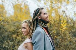 一对快乐的夫妇紧接站立 新娘和新郎与获得的dreadlocks乐趣在自然 婚姻的仪式户外 库存照片