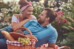 一对愉快的中年夫妇的画象在浪漫约会期间的户外,享受野餐,当说谎在时的一条毯子 免版税图库摄影