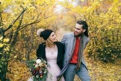 一对愉快的夫妇在秋天森林的一串足迹走与dreadlocks的新娘和新郎看彼此  免版税库存图片
