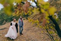 一对愉快的夫妇在秋天森林的一串足迹走与dreadlocks的新娘和新郎看彼此  库存图片