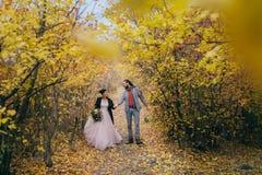 一对愉快的夫妇在秋天森林的一串足迹走与dreadlocks的新娘和新郎看彼此  库存照片