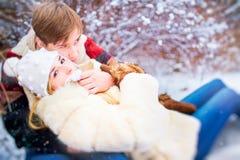 一对愉快的夫妇在胜利的一个公园乘坐在雪的一个雪撬 免版税库存照片