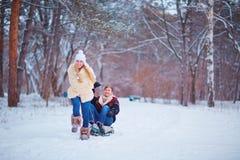 一对愉快的夫妇在胜利的一个公园乘坐在雪的一个雪撬 库存照片