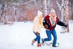 一对愉快的夫妇在胜利的一个公园乘坐在雪的一个雪撬 库存图片