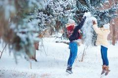 一对愉快的夫妇在胜利的一个公园乘坐在雪的一个雪撬 免版税库存图片