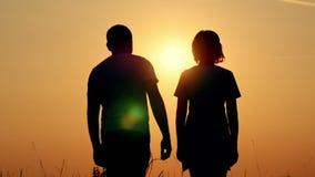 一对愉快的夫妇的慢动作剪影 人拥抱一个女孩反对日落 爱恋的人妇女
