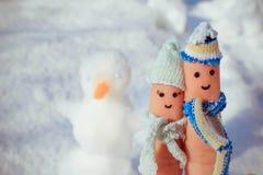 一对愉快的夫妇的手指艺术在雪和雪人背景的  库存图片