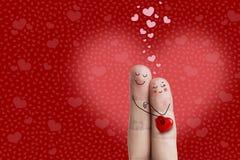 一对愉快的夫妇的手指艺术 恋人是接受和拿着红色心脏 图象纵向股票妇女年轻人 免版税库存图片