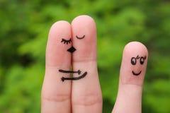 一对愉快的夫妇的手指艺术 拥抱愉快的夫妇亲吻和 另一个女孩看他们并且高兴 免版税库存照片