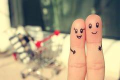 一对愉快的夫妇的手指艺术 男人和妇女在背景购物车拥抱 免版税图库摄影