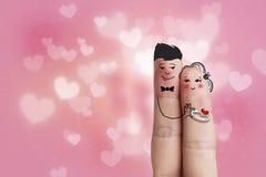 一对愉快的夫妇的概念性手指艺术 人给一个圆环 图象纵向股票妇女年轻人 免版税库存照片