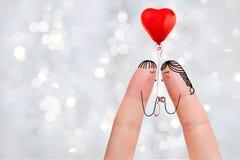 一对愉快的夫妇的概念性手指艺术 恋人是亲吻和拿着红色气球 图象纵向股票妇女年轻人 免版税库存照片