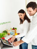 一对愉快的夫妇的纵向在厨房里 免版税库存图片