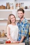 一对愉快的微笑的夫妇的画象在厨房的 免版税库存照片
