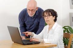 一对愉快的资深夫妇的画象使用膝上型计算机的 库存图片
