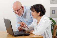一对愉快的资深夫妇的画象使用膝上型计算机的 免版税库存照片