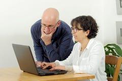 一对愉快的资深夫妇的画象使用膝上型计算机的 免版税图库摄影