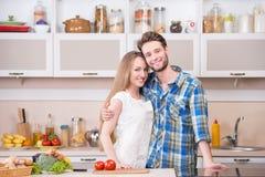 一对愉快的年轻夫妇的画象在厨房的 库存照片