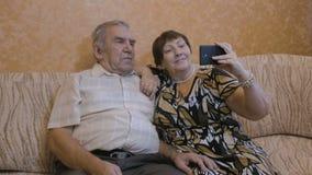 一对成人夫妇做selfie 为照片使用一个智能手机 股票录像