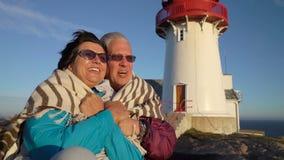 一对成熟夫妇敬佩在沿海的日落与一座老灯塔 影视素材