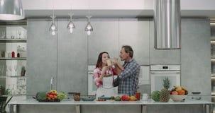 一对成熟夫妇的Romatinc时间在厨房饮用的圆滑的人早餐和亲吻可爱 股票录像