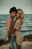 一对拥抱的夫妇的纵向在海滩的 免版税图库摄影