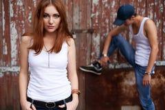 一对时髦的夫妇的感情纵向在突出最近的木头的牛仔裤的 免版税库存图片