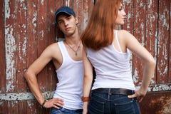 一对时髦的夫妇的感情纵向在突出最近的木头的牛仔裤的 免版税图库摄影