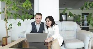 一对有吸引力的夫妇坐长沙发在大厅里并且谈论生意 股票录像